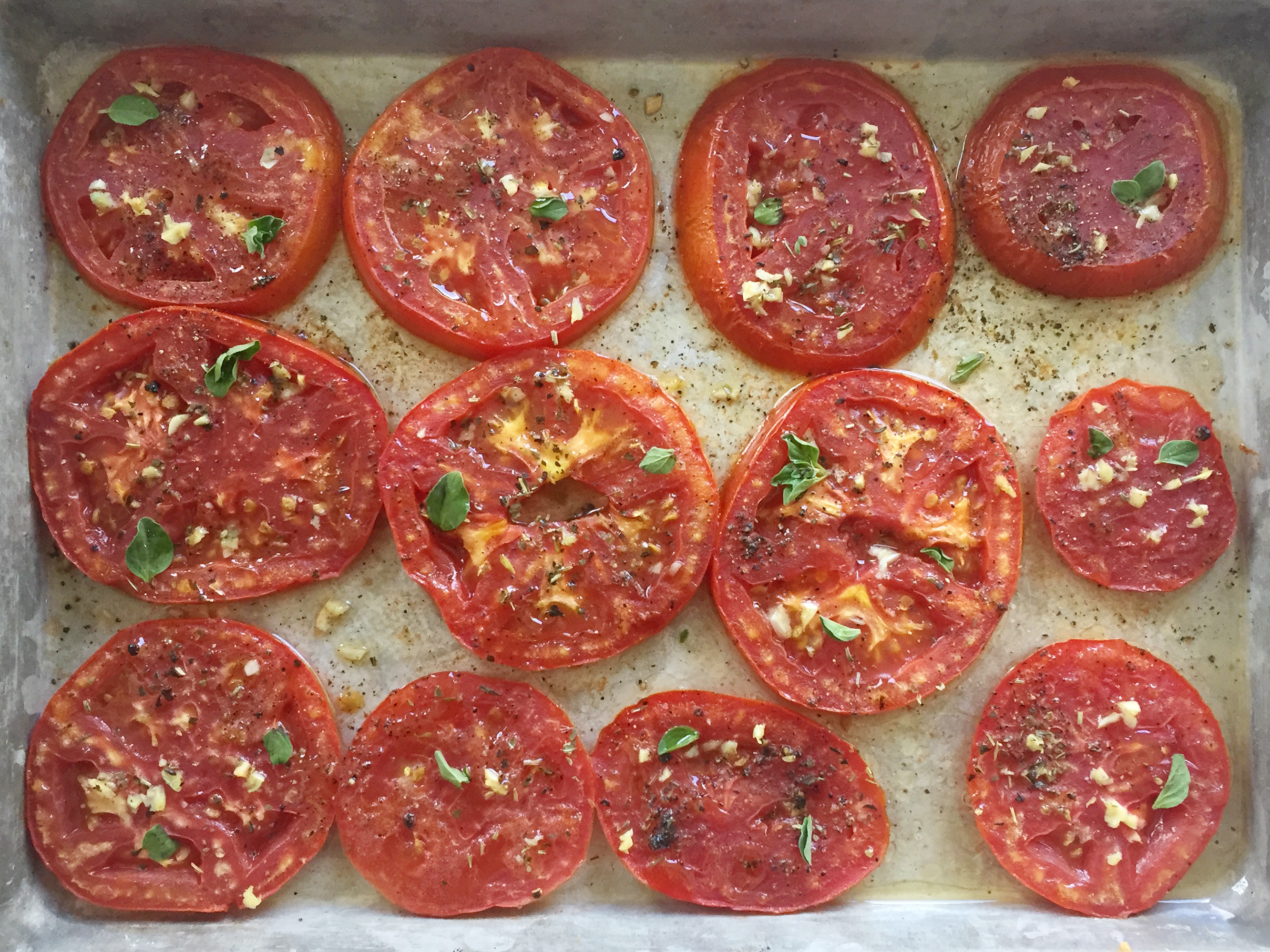 Baked tomato slices on a sheet tray.