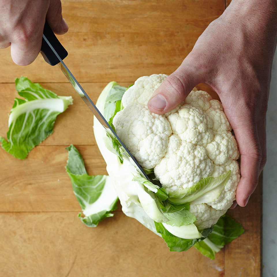 removing the leaves from cauliflower with a knife