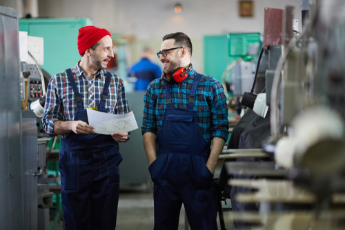 A small business owner and a consultant chat in an industrial workshop