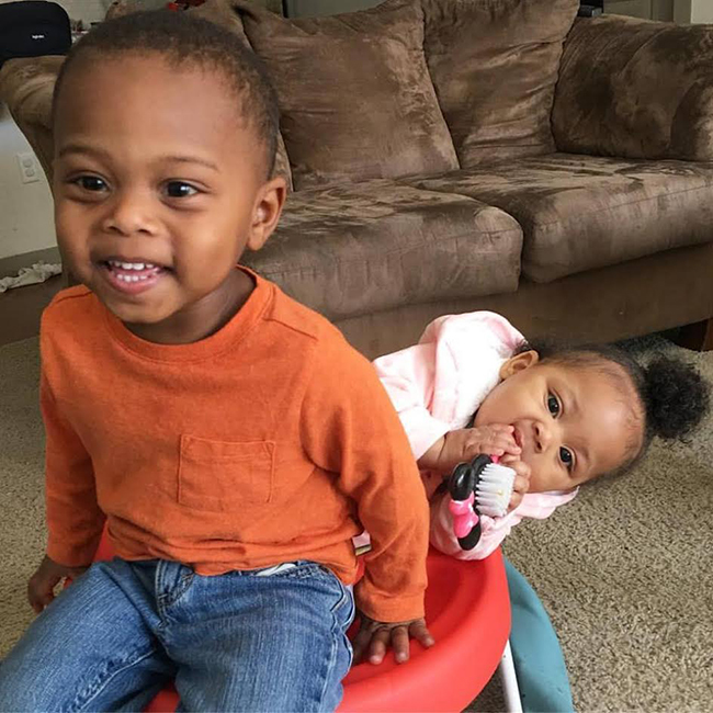 two african-american toddlers smilling and playing