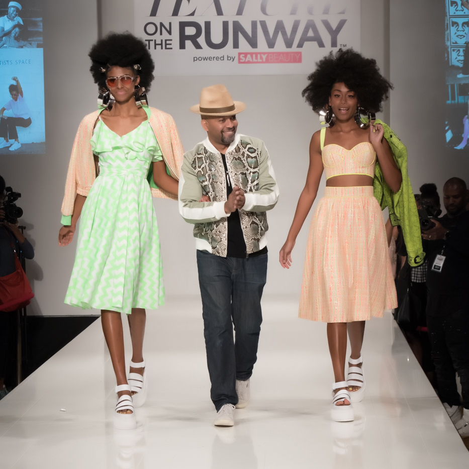 Stylist David De LaCrus walks a runway flanked by two black models with styled afros